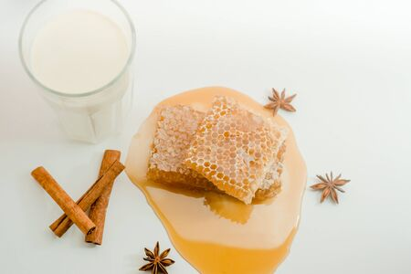 Large pieces of natural honeycombs next to a glass of milk. Imagens - 135223624