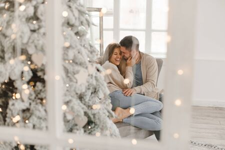 Young beautiful happy couple, sitting on the couch near the Christmas tree. Archivio Fotografico - 136227593