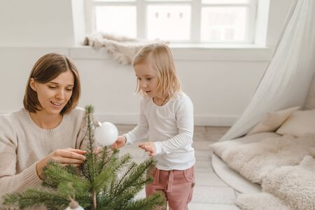 Cute little baby girl with her mom play in a spacious bright minimalistic childrens room.