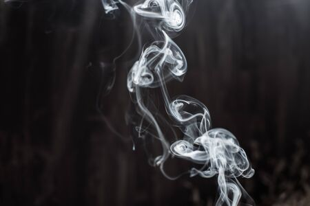 Image of backlit puffs of smoke, on a dark background. Archivio Fotografico - 136719082