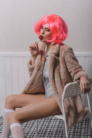 Young attractive woman in a bright pink wig, golf and faux fur coat. Archivio Fotografico - 137275557