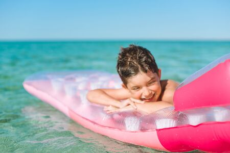 Cheerful boy swims in the sea on a inflatable mattress. Archivio Fotografico - 137363325