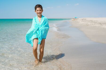 A cheerful kid on the beach wrapped in a bright beach towel. Archivio Fotografico - 137599012