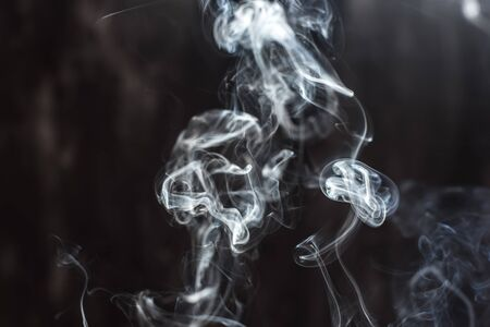 Image of backlit puffs of smoke, on a dark background. Archivio Fotografico - 137803097