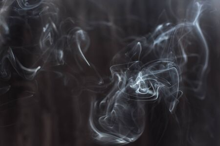 Image of backlit puffs of smoke, on a dark background.