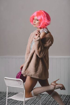 Young attractive woman in a bright pink wig, golf and faux fur coat.