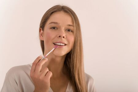 Portrait of a young beautiful woman with lip gloss in her hand. Banque d'images - 140551691