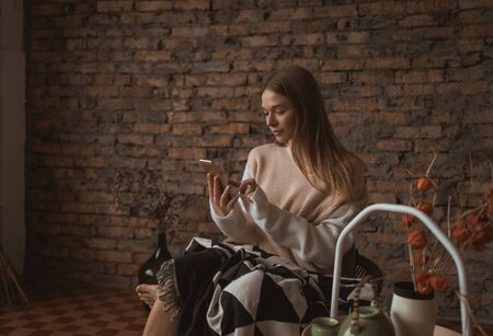 A young attractive woman sits in a chair with a smartphone in her hands. Banque d'images - 140551694