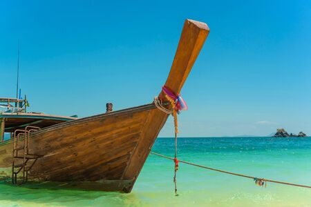 Traditional Thai longtail boat moored on exotic beach. Banque d'images - 140551595