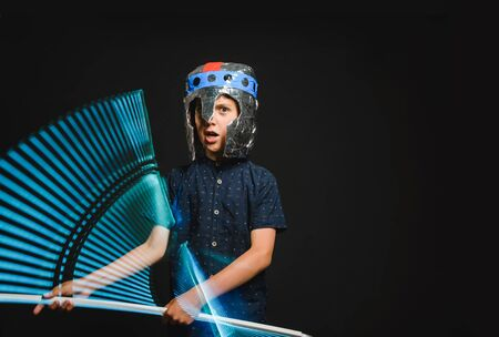 A kid with a light saber in his hands play in a superhero battle. Banque d'images - 140741335