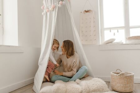 Cute baby girl with her mom play in a minimalistic childrens room. Banque d'images - 140216353