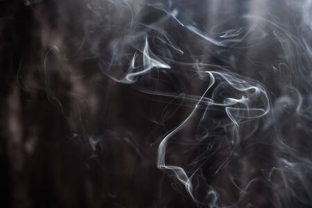 Image of backlit puffs of smoke, on a dark background. Banque d'images - 140394679