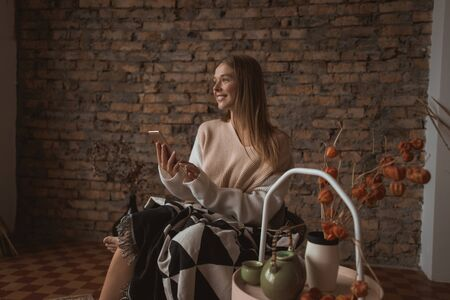 A young attractive woman sits in a chair with a smartphone in her hands. Stock Photo