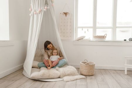 Cute baby girl with her mom play in a minimalistic childrens room.