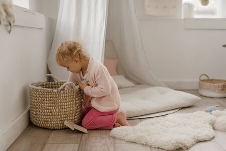 Cute little baby girl plays in a spacious bright minimalistic children's room.