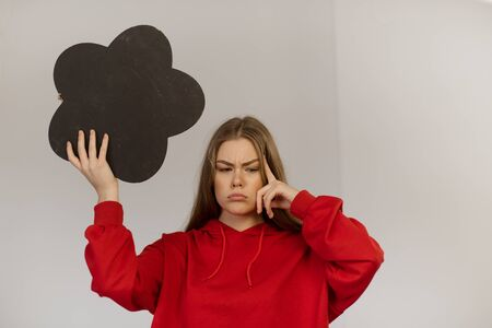 A teenager girl is holding a chalk board in the shape of a thought bubble. 版權商用圖片
