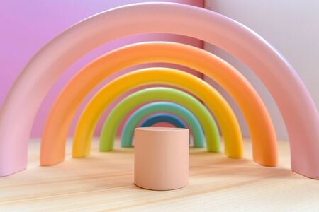 Abstract figures from elements of the childrens designer wooden pastel rainbow on a wooden podium.