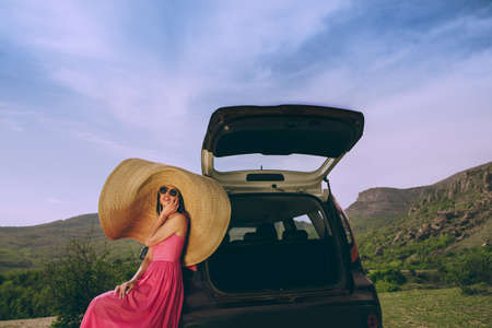 Young beautiful woman in a dress and a wide-brimmed hat near a hatchback car on a background of a mountain landscape. Stock fotó
