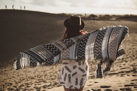 young woman from backwards with bandana and hat in the desert at sunset on windy day Stock Photo