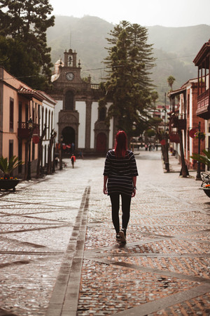young redhead woman walking main street with typical canarian houses in Teror Gran Canary Canary Islands Spain Reklamní fotografie - 120253660