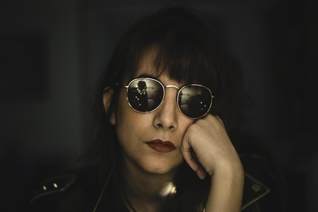 Rock woman resting on her hand with sunglasses and red lips Imagens