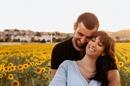 Young couple in love hugging and smiling in the sunflower field at sunset