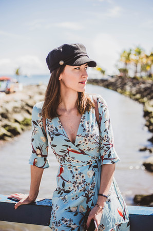pretty young woman in a tropical place looking at her side with a black cap