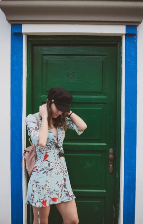 beautiful model in a green door looking at the floor with a black cap