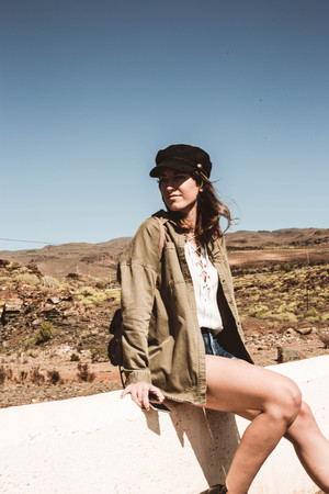 Fashion woman sitting on a curb in a desert area