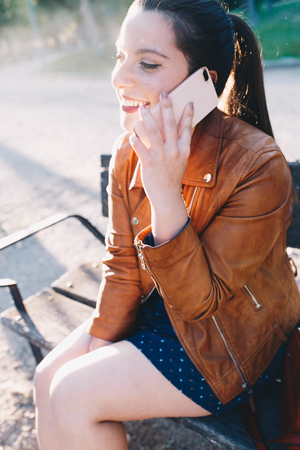 Happy young woman with leather jacket talking on the smart phone in a city park sitting on a bench