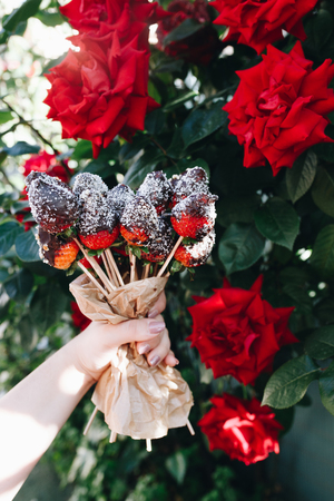 A bouquet of chocolate covered strawberries with different toppings: chocolate coconut cocoa almonds nuts, close up of red roses