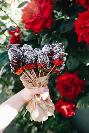 A bouquet of chocolate covered strawberries with different toppings: chocolate coconut cocoa almonds nuts close up of red roses