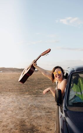 Young traveler having fun with the guitar in the  4x4 car making a wanderlust vacation at sunset in summer
