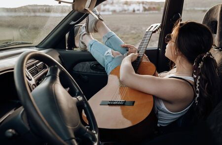 Young traveler playing the guitar inside the 4x4 car, making a wanderlust vacation at sunset