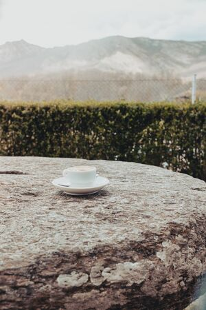 Morning hot cup of coffee on a old stone table with mountain background at sunrise