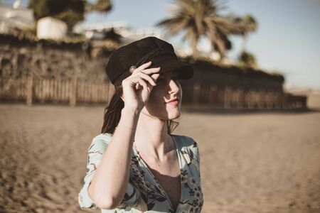 beautiful young woman portrait in the desert touching her black cap Reklamní fotografie