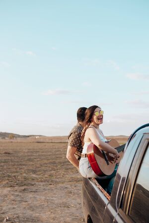 Young travelers lovers having fun playing the guitar on top of 4x4 car. Couple making a wanderlust vacation at summer