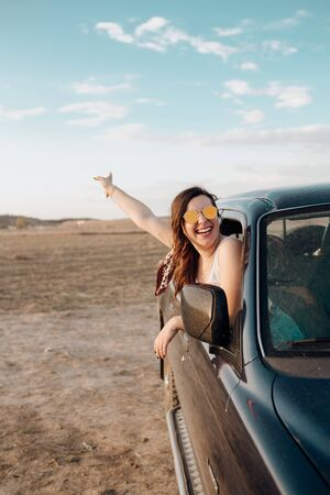 Young traveler woman having fun with the guitar in the jeep 4x4 car making a wanderlust vacation at sunset in summer