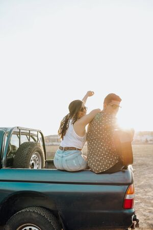 Back view of young travelers lovers having fun with the guitar on top of jeep 4x4 car. Couple making a wanderlust vacation on sunset