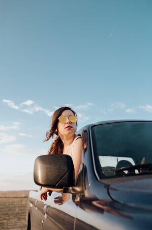 Young traveler woman with sunglasses in the 4x4 car making a wanderlust vacation at sunset