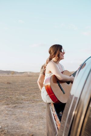 Young traveler woman having fun playing the guitar on top of jeep 4x4 car. Couple making a wanderlust vacation on sunset at summer