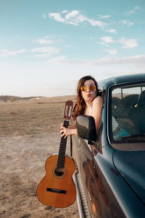 Young traveler woman having fun with the guitar in the 4x4 car making a wanderlust vacation at sunset in summer