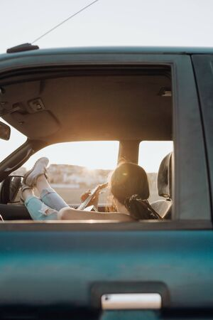 Young traveler woman playing the guitar inside the 4x4 car making a wanderlust vacation at sunset Reklamní fotografie