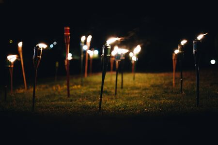 Burning torches at night in the grass with yellow flames and highlights