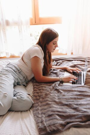 beautiful young woman lying in her cozy bed writing on her laptop