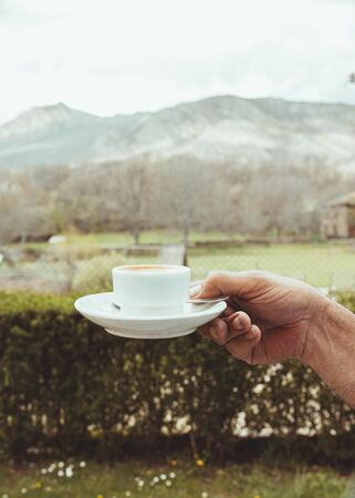 Man hand holding a cup of coffee on a old stone table with mountain background at sunrise