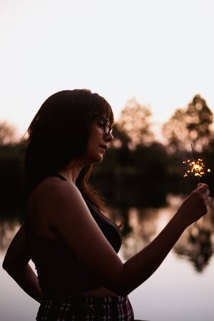 Brunette woman at sunset on a lake with a sparkler a summer day Reklamní fotografie