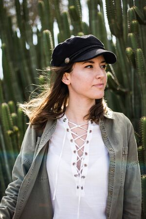 portrait of a pretty young woman with black cap near cactus