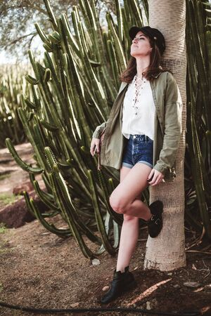 pretty young woman with black cap resting on the trunk of a tree with cactus Reklamní fotografie