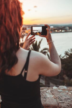 Beautiful girl taking a photo of sea landscape by mobile phone, warm light of the sunset evening Reklamní fotografie - 127261239
